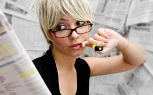 Une femme souligne des textes dans une grande quantité de journaux
