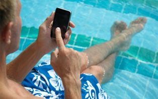 A young man relaxing in the pool with an iPhone